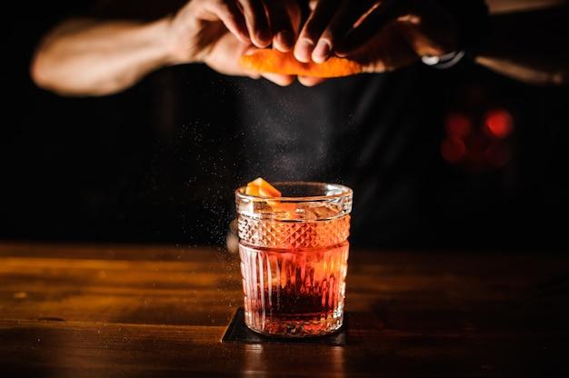 Barman com cocktail e casca de laranja, a preparar cocktails no bar