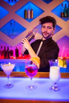 Barman com coqueteleira no balcão de bar