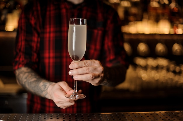 Barman com tatuagens segurando um coquetel francês 75