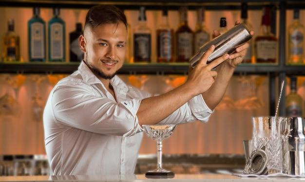 Barman com um sorriso encantador prepara uma deliciosa bebida agitando