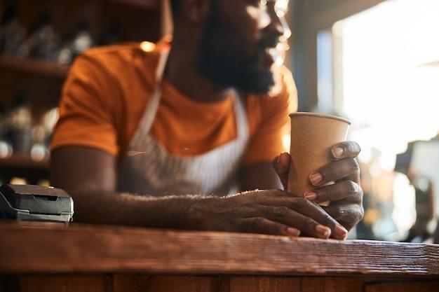 Barman com uma xícara de café em frente ao balcão do bar