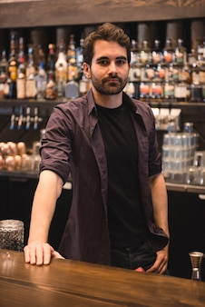 Barman confiante em pé no balcão do bar