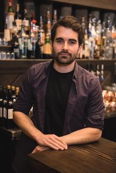 Barman confiante em pé no balcão do bar