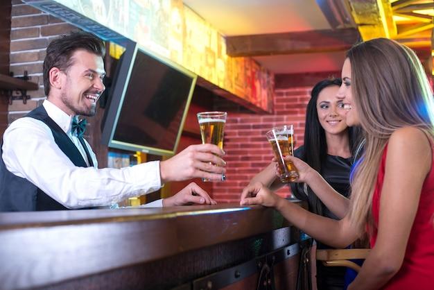 Barman considerável do smiley que estica para fora a cerveja.