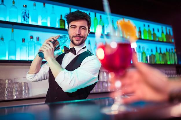 Barman considerável que prepara o cocktail no balcão de bar