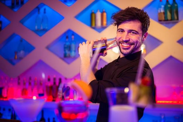 Barman considerável que prepara o cocktail