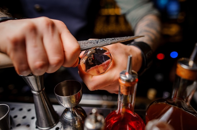 Barman corta o gelo com uma faca especial para preparação de coquetel