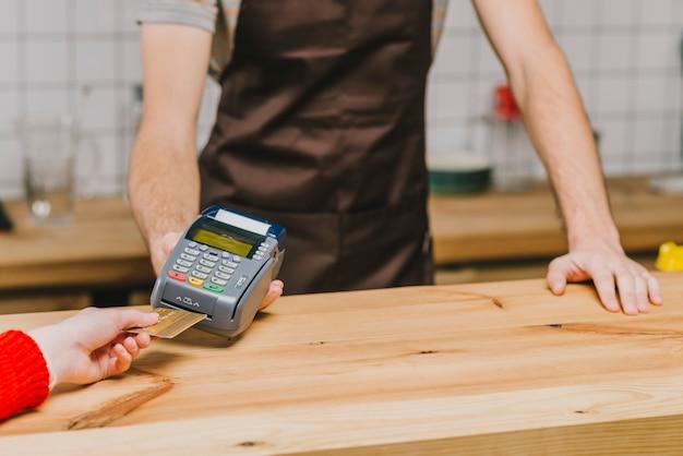 Barman da colheita que aceita o pagamento com cartão de crédito