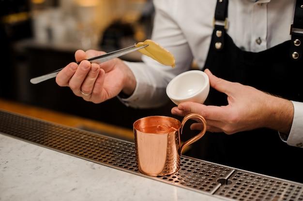 Barman de avental fazendo coquetel alcoólico com gengibre usando pinças