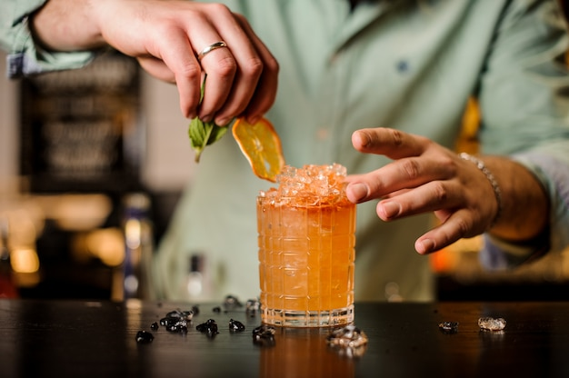 Barman decora um cocktail sem rosto