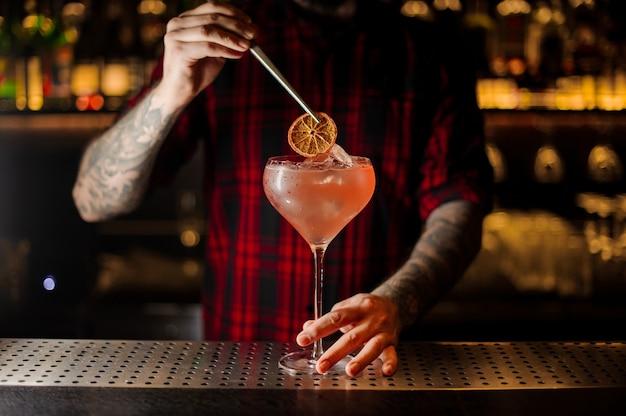 Barman decorando coquetel alcoólico doce com uma rodela de laranja seca no balcão do bar