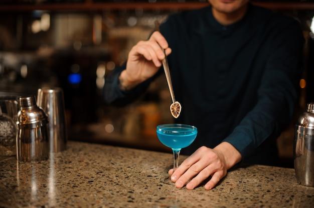 Barman, decorando um copo de coquetel de verão fresco com licor azul usando uma fatia de laranja