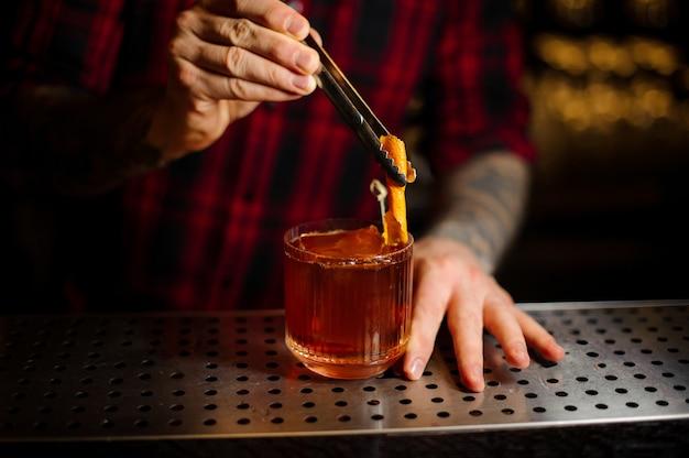 Barman decorando uma taça de coquetel com uísque com casca de laranja fresca no balcão do bar