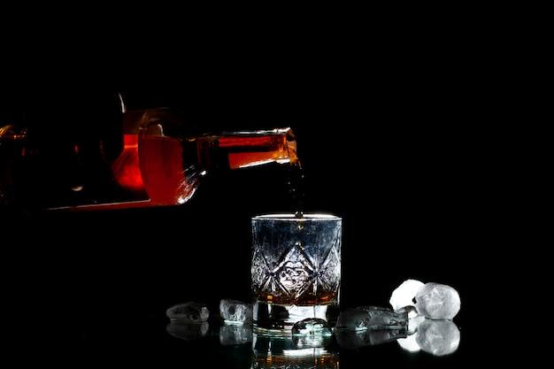 Barman derrama uísque em um copo com gelo