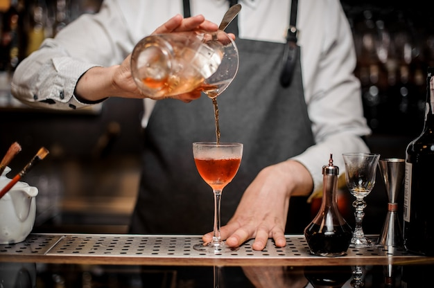 Barman, derramando bebida alcoólica doce fresca no copo de coquetel