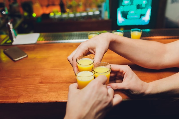Barman, derramando bebida alcoólica forte em pequenos copos no bar, tiros.