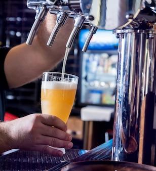 Barman, derramando cerveja em copos no bar. restaurante.