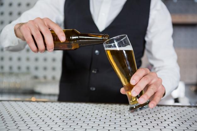 Barman, derramando cerveja em vidro