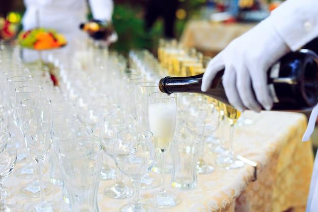 Barman, derramando champanhe em copos