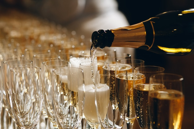 Barman, derramando champanhe ou vinho em taças de vinho em cima da mesa na cerimônia de casamento solene ao ar livre