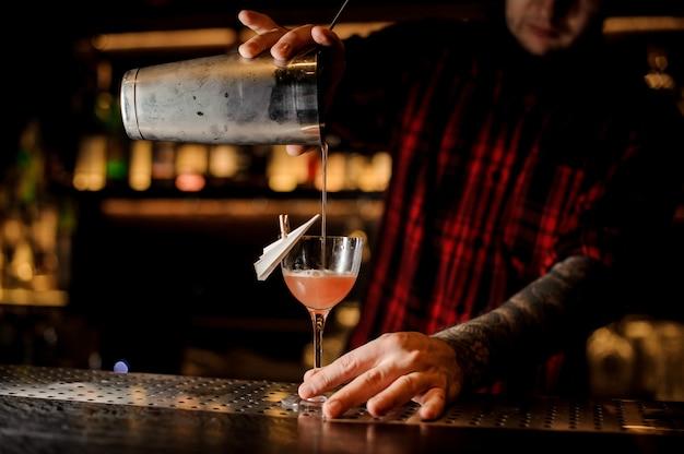 Barman, derramando cocktail de avião de papel em um copo decorado