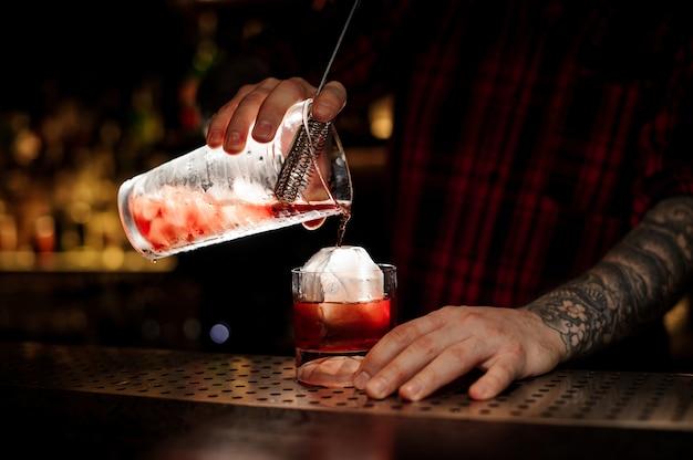 Barman, derramando cocktail de uísque vermelho forte fresco em um copo