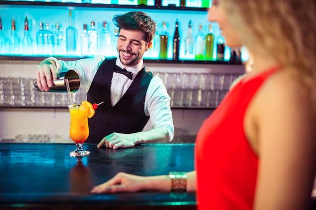 Barman, derramando cocktail em vidro para cliente