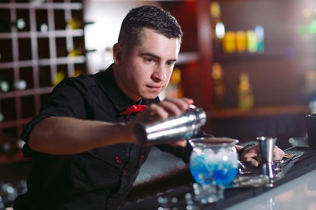 Barman, derramando cocktail fresco em copo chique