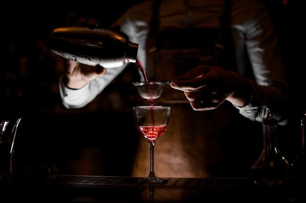 Barman, derramando coquetel com peneira em vidro