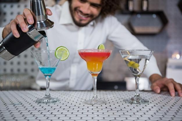 Barman, derramando coquetel em copos
