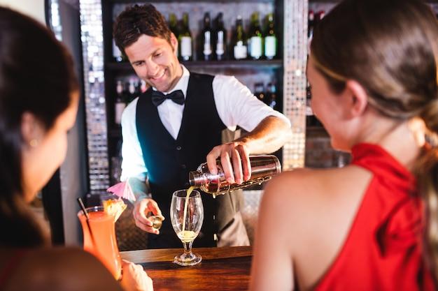 Barman, derramando coquetel em vidro no balcão de bar