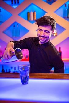 Barman, derramando coquetel em vidro