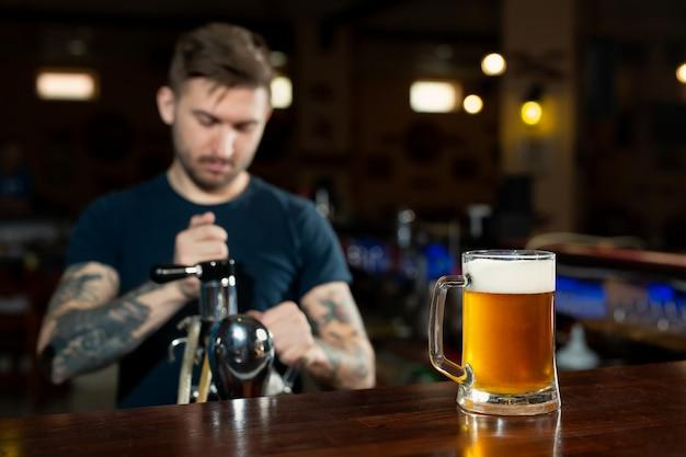 Barman, derramando da torneira cerveja fresca no copo no pub