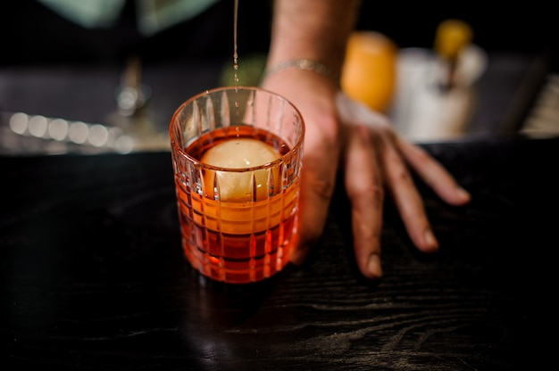 Barman, derramando o coquetel no copo com bola de gelo