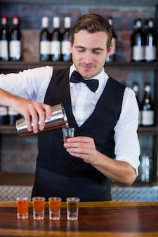 Barman, derramando tequila em copos de shot