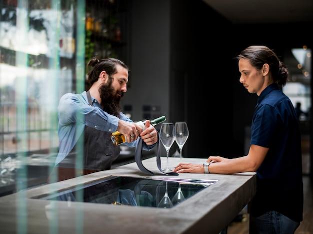 Barman, derramando um vinho para o copo