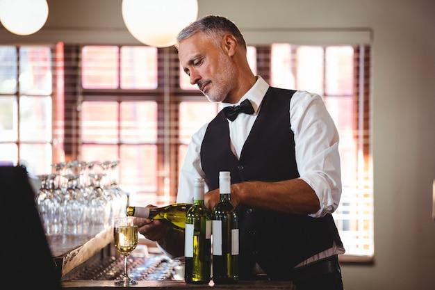 Barman, derramando vinho tinto em um copo