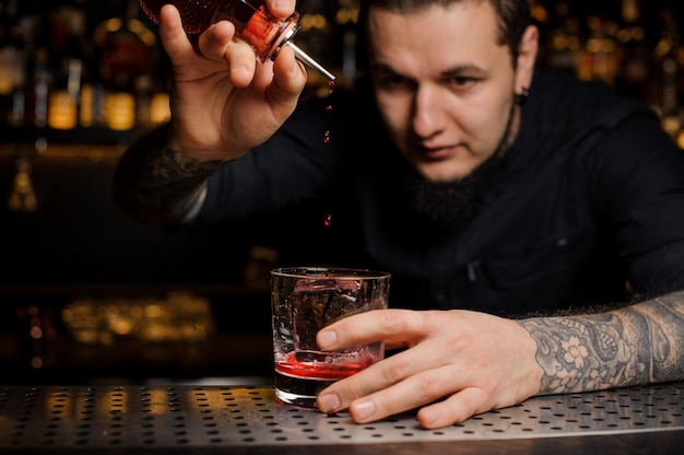 Barman, derramando xarope em um copo com cubo de gelo