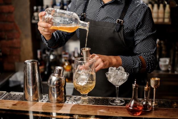 Barman, derramando xarope no copo grande de coquetel