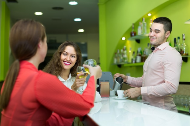 Barman e mulheres sorridentes no bar