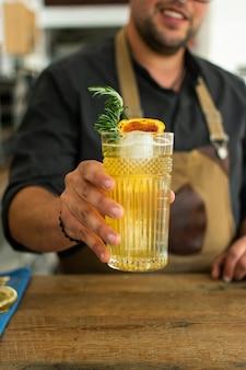 Barman em bar ou restaurante preparando um coquetel de gin tônica.