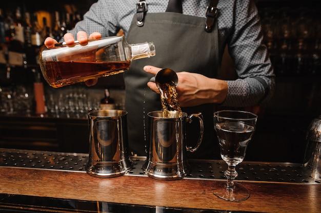 Barman em fazer avental e coquetel alcoólico