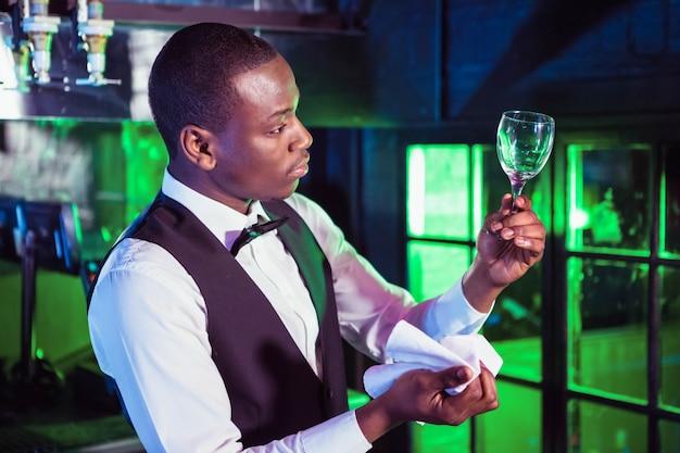 Barman em pé no balcão do bar e verificar um copo de vinho após a limpeza