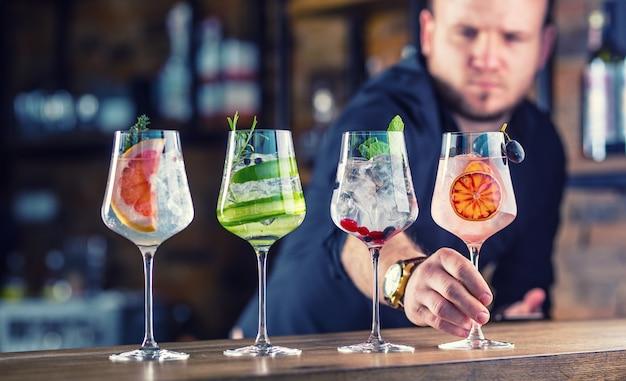 Barman em um bar ou restaurante preparando drinques de coquetel gin tônico em taças de vinho.