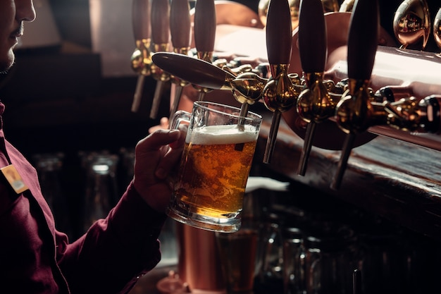 Barman enche a caneca de cerveja da torneira de cerveja