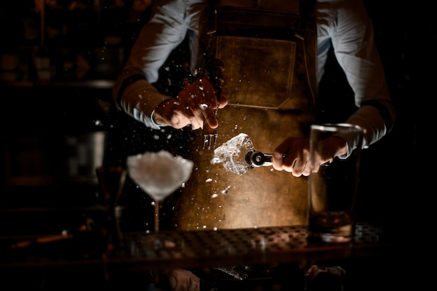 Barman, esmagando um cubo de gelo com selecionador