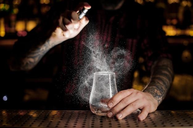 Barman espargindo amargo em um copo de coquetel baixo e vazio no balcão do bar contra as luzes do pub