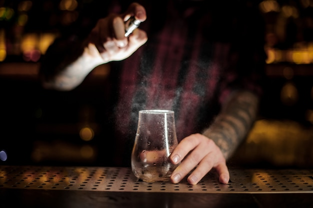 Barman espargindo amargo em uma taça de coquetel baixa e vazia no balcão do bar contra as luzes