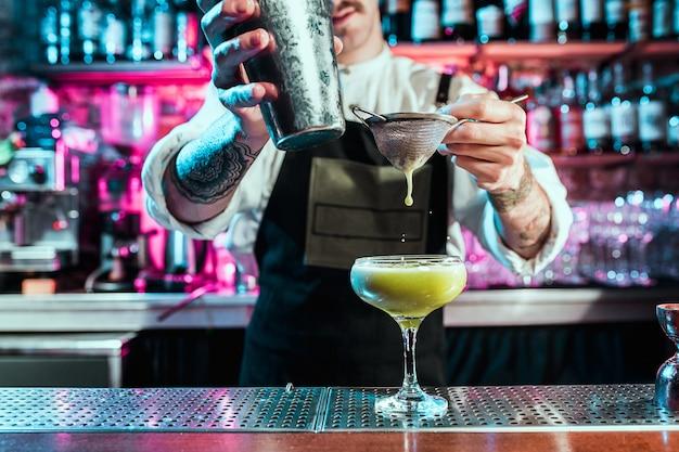 Barman especialista está fazendo coquetéis em uma boate ou bar. copo de coquetel ardente no balcão do bar no contexto das mãos dos bartenders com fogo. conceito do dia do barman
