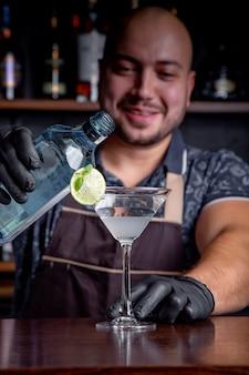 Barman especialista está fazendo um cocktail na boate. barman profissional no trabalho em bar derramando bebida doce em vidro na festa na boate. barman está decorando um coquetel.
